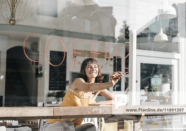 Frau sitzt im Café und schreibt das Wort Kaffee auf die Fensterscheibe.