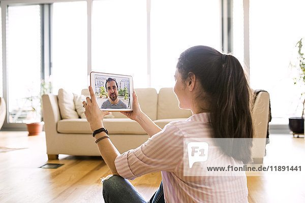 Young woman using tablet for video chat at home