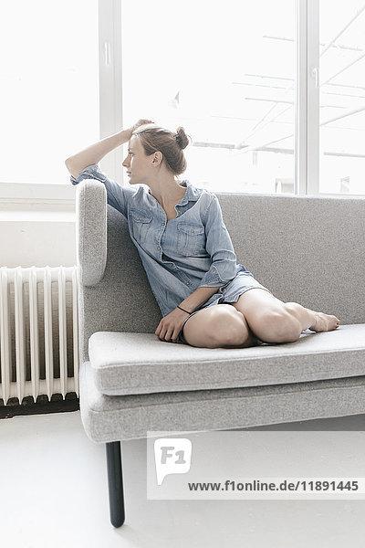 Frau sitzt auf der Couch in einem Loft und schaut aus dem Fenster.