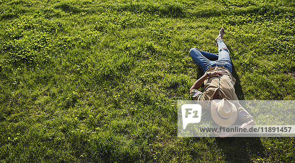 Young man sleeping on a meadow  top view