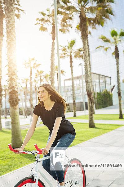 Lächelnde junge Frau auf Fixie Bike