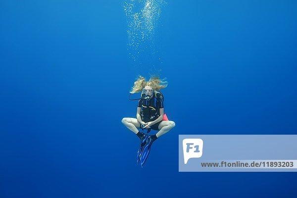 Taucherin in einer Lotoshaltung für einen Sicherheitsstopp  im blauen Wasser  Indischer Ozean  Malediven  Asien