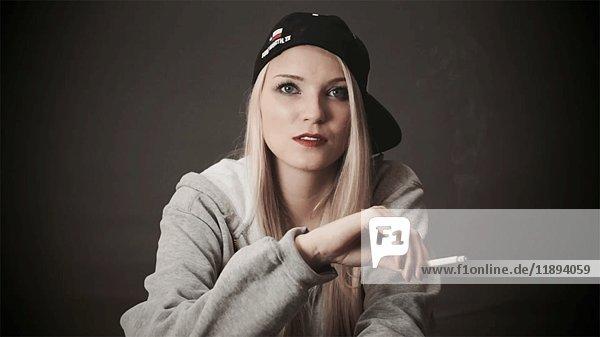 Woman in Baseball Cap Smoking Cigarette