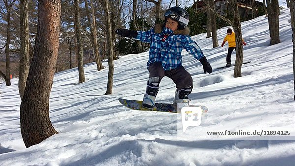 Boy Jumping with Snowboard while Young Woman snowboards Behind him
