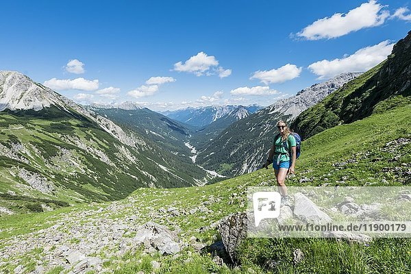 Wanderin steht auf kleinem Felsen  Ausblick ins Tal mit Allgäuer Alpen  Bad Hindelang  Allgäu  Bayern  Deutschland  Europa
