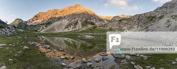 Wanderin sitzt auf Felsen  Berge im Abendlicht  Glasfelderkopf links  mitte Fuchskarspitze  Spiegelung im Bergsee beim Printz-Luitpolt-Haus  Bad Hindelang  Allgäu  Bayern  Deutschland  Europa