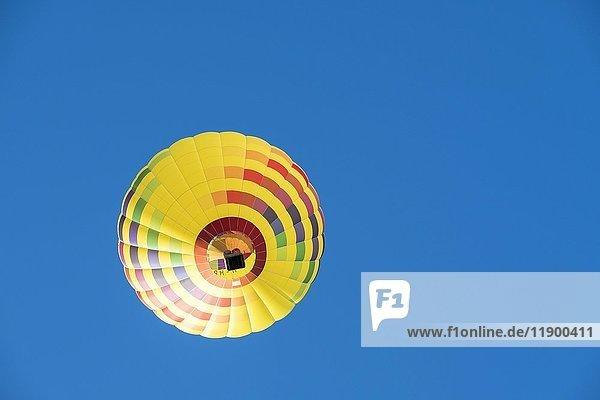 Gelber Heißluftballon vor blauem Himmel