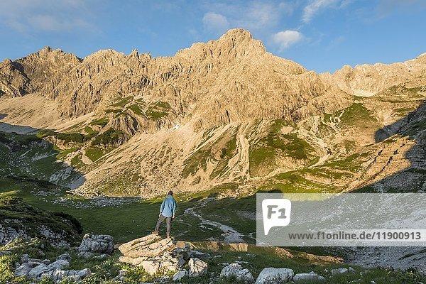 Wanderer auf Felsen  Berge im Abendlicht  Glasfelderkopf links  mitte Fuchskarspitze  Bergsee beim Printz-Luitpolt-Haus  Bad Hindelang  Allgäu  Bayern  Deutschland  Europa