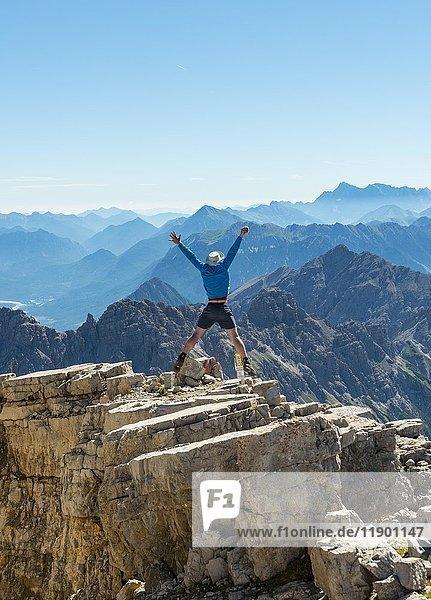Wanderer streckt Arme in die Luft  Luftsprung  Berge und Alpen  Gipfel des Hochvogel  Allgäu  Allgäuer Hochalpen  Bayern  Deutschland  Europa
