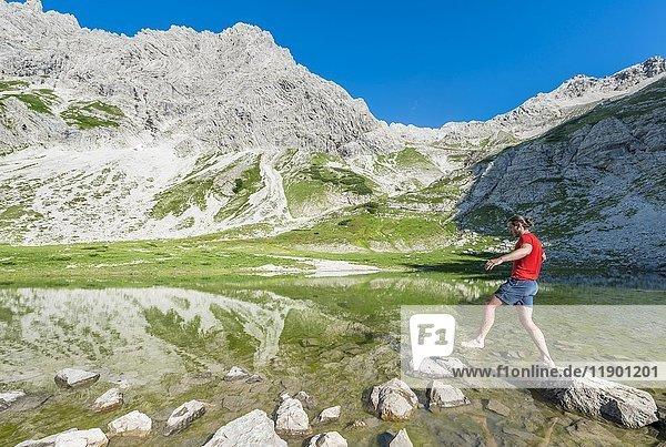 Wanderer springt auf einen Stein  Bergsee beim Printz-Luitpolt-Haus  Allgäuer Alpen  Bad Hindelang  Allgäu  Bayern  Deutschland  Europa