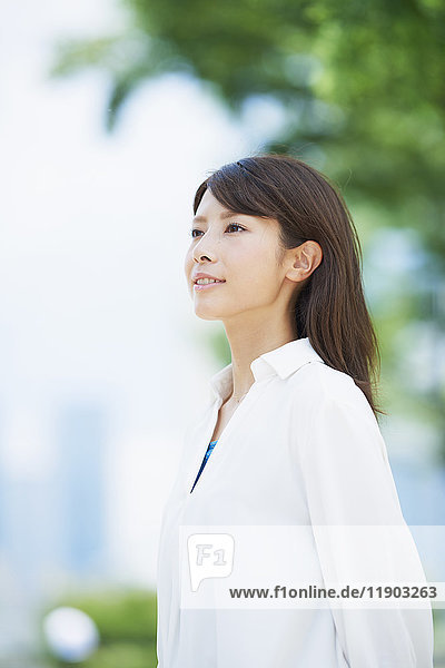 Portrait of young Japanese woman and fresh green  Tokyo  Japan