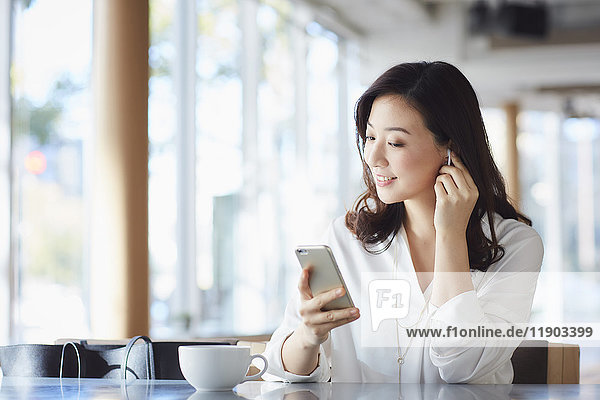 Japanese woman with smartphone in a stylish cafe