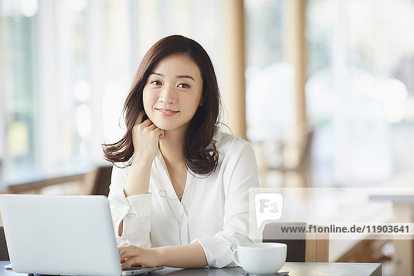 Japanese woman with laptop in a stylish cafe