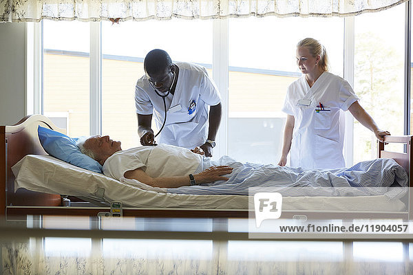 Krankenschwester bei der Untersuchung eines älteren Mannes auf dem Bett in der Krankenstation