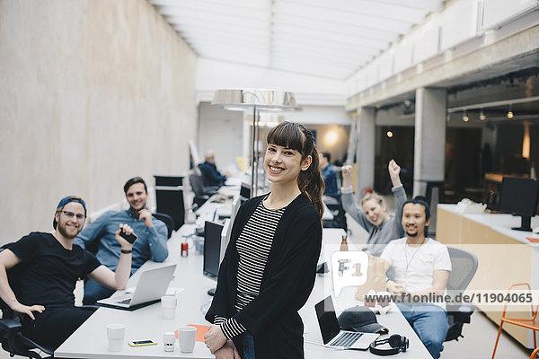 Porträt einer glücklichen Programmiererin mit Kollegen am Schreibtisch im Hintergrund