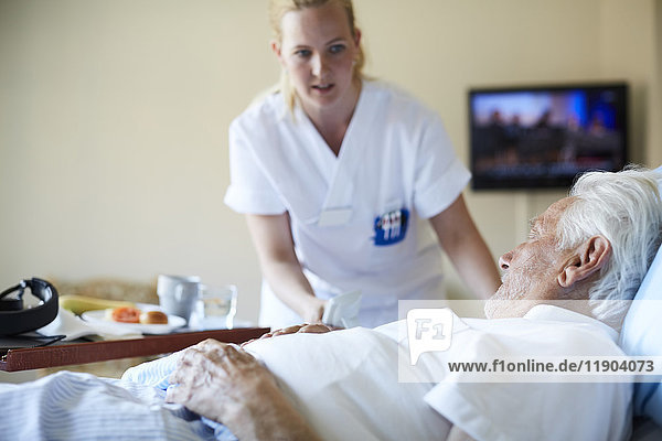 Krankenschwester serviert Frühstück für Senioren auf der Krankenstation