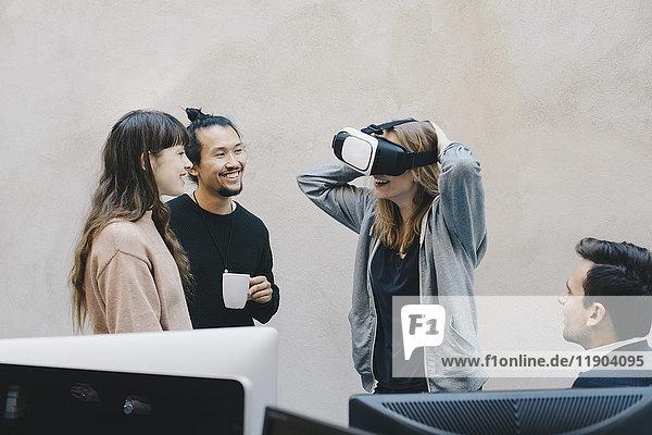 Glücklicher Computerprogrammierer mit VR-Brille im Gespräch mit Kollegen im Büro
