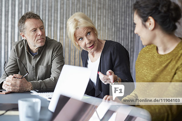 Senior businesswoman discussing with colleagues in board room