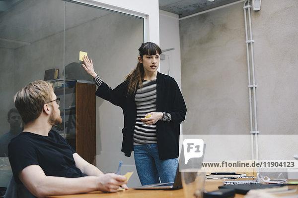 Computerprogrammiererin mit Haftnotiz bei der Präsentation vor Kollegen im Büro