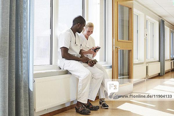 Volle Länge der Krankenschwestern und Krankenpflegerinnen auf dem Fensterbrett im Flur des Krankenhauses.