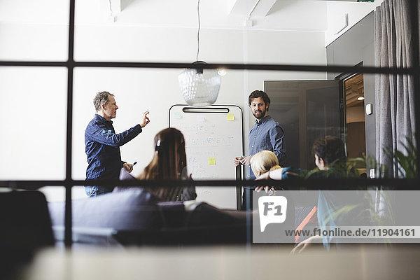 Niederwinkelansicht der männlichen Profis  die den weiblichen Kollegen aus dem Glas im Sitzungssaal bei der kreativen
