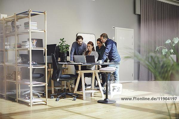 Geschäftsleute mit Laptop am Schreibtisch im Kreativbüro