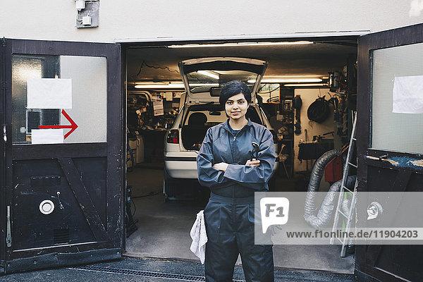 Porträt einer selbstbewussten Mechanikerin am Eingang der Autowerkstatt