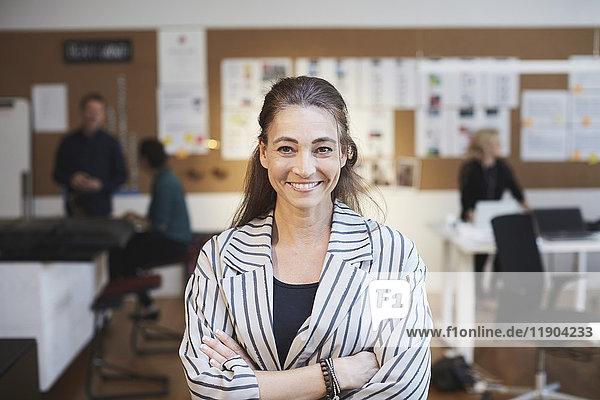 Porträt einer lächelnden Geschäftsfrau mit Kollegen im Hintergrund im Kreativbüro