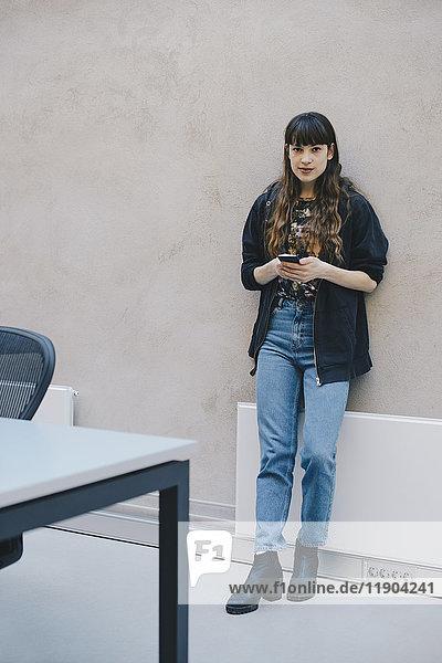 Vollständiges Porträt einer Computerprogrammiererin  die ein Smartphone hält  während sie an einer beigen Wand im Büro steht.