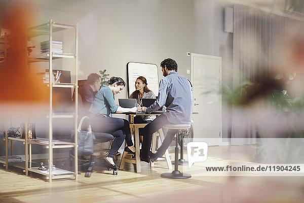 Geschäftsleute diskutieren mit Laptops am Schreibtisch im Kreativbüro.