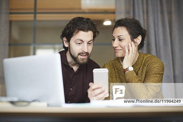 Mittlere erwachsene Geschäftskollegen mit Handy im Kreativbüro