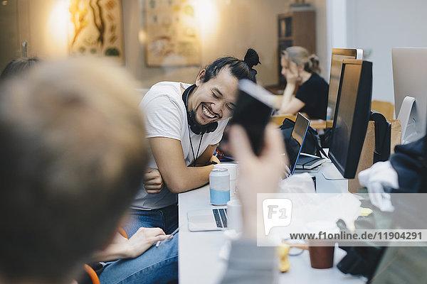 Glücklicher Computerprogrammierer sitzt mit Kollegen am Schreibtisch im Büro