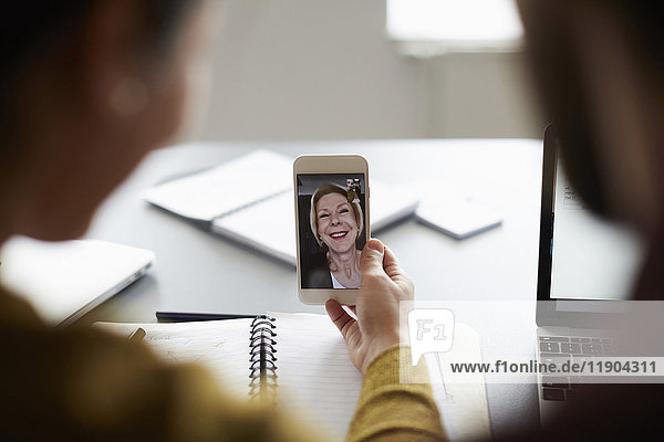 Videokonferenz mit hochrangiger Geschäftsfrau auf dem Smartphone im Vorstandszimmer