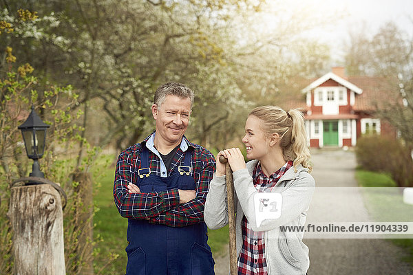 Confident farmer looking at smiling daughter while standing on footpath
