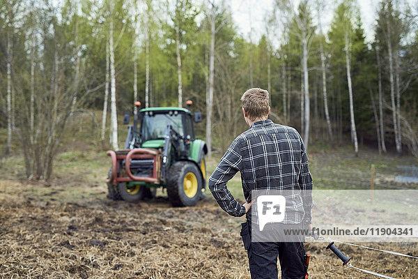 Rückansicht des Landwirts  der das Stahlseil auf dem Feld hält.