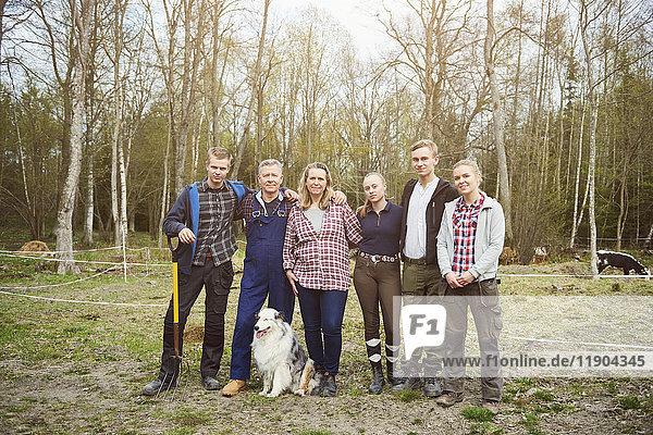 Volle Länge des Bauern mit Familie auf dem Feld gegen Bäume stehend