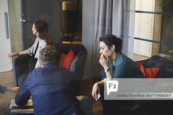 Profis im Sitzungssaal während der Besprechung im Kreativbüro aus Glas gesehen