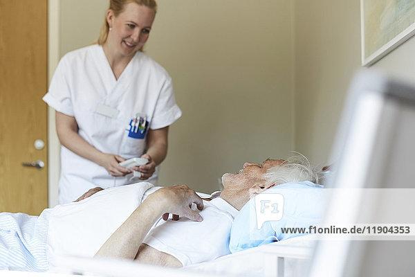Lächelnde Krankenschwester  die das Bett eines älteren Mannes in der Krankenstation anpasst.