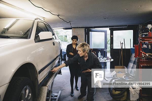 Mechanikerin beim Zeigen des Autos zum Kunden in der Autowerkstatt