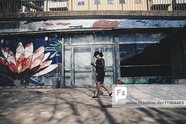 Seitenansicht der jungen Frau mit dem Handy beim Gehen auf dem Fußweg durch das Gebäude Seitenansicht der jungen Frau mit dem Handy beim Gehen auf dem Fußweg durch das Gebäude