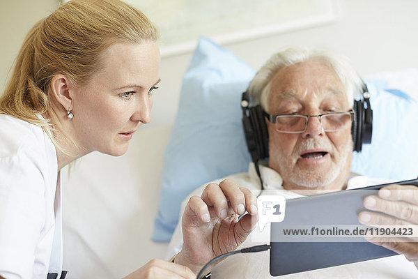 Krankenschwester unterstützt älteren Mann bei der Verwendung von digitalen Tabletten auf dem Krankenhausbett