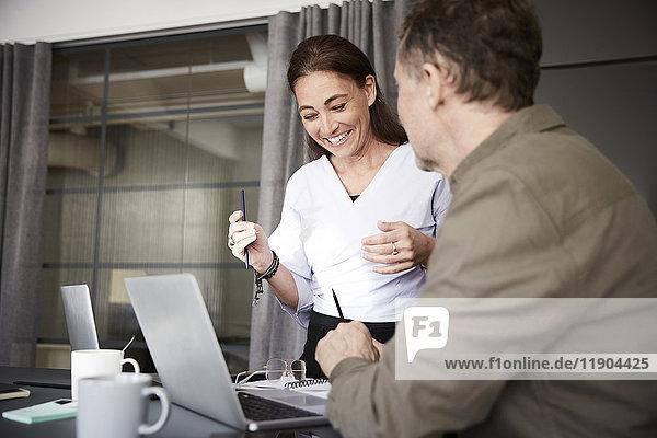 Lächelnde reife Profis mit Laptop am Konferenztisch im Sitzungssaal