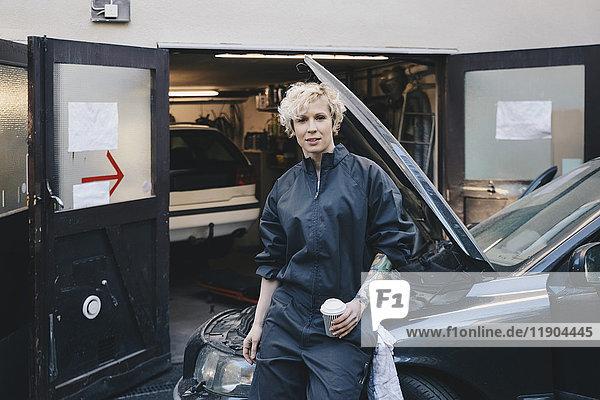 Porträt einer selbstbewussten Mechanikerin  die sich außerhalb der Werkstatt auf das Auto stützt.