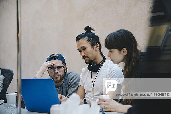 Computerprogrammierer mit Laptop am Schreibtisch im Büro
