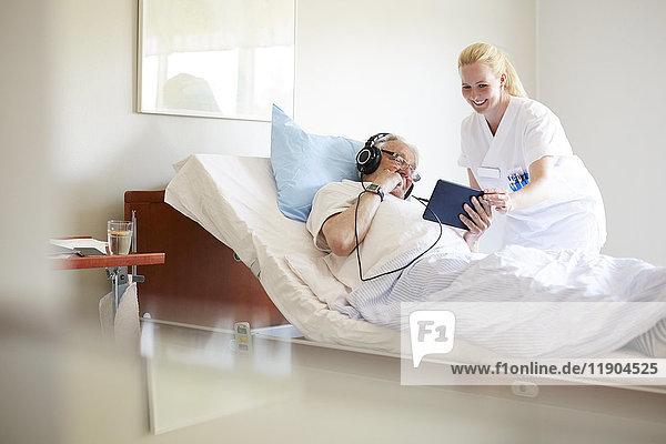 Fröhliche Krankenschwester hilft dem älteren Mann bei der Verwendung von digitalen Tabletten auf dem Krankenhausbett