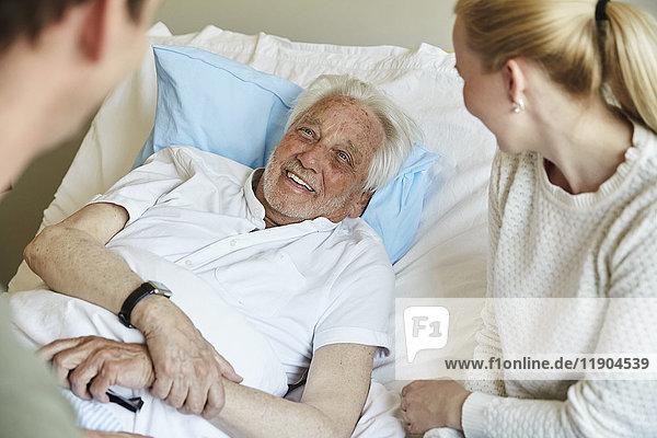 Glücklicher älterer Mann  der mit einem Paar spricht  während er auf dem Bett in der Krankenstation liegt.