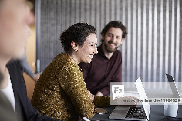 Lächelndes  kreatives Business-Team sitzend mit Laptop am Konferenztisch im Sitzungssaal