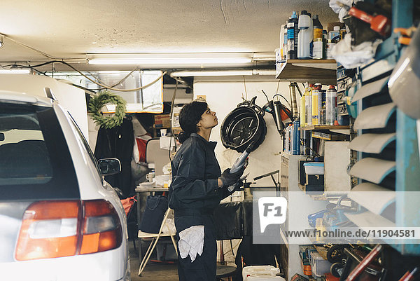 Side view of female mechanic looking at bottles on shelf at auto repair shop