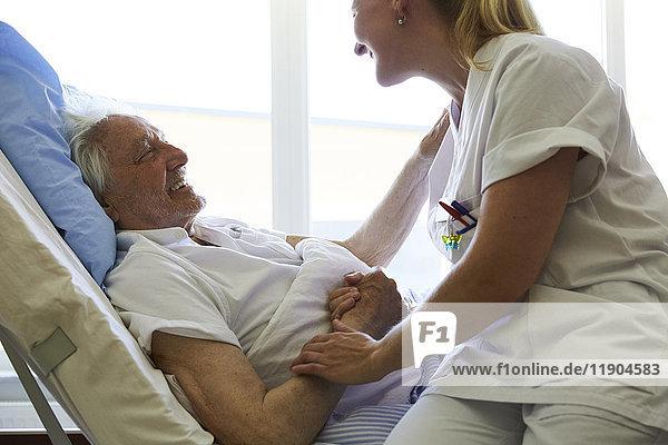 Seitenansicht eines glücklichen älteren Mannes im Gespräch mit einer Krankenschwester im Krankenhausbett