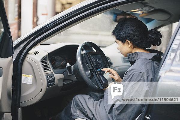 Seitenansicht der Mechanikerin im Auto mit digitalem Tablett